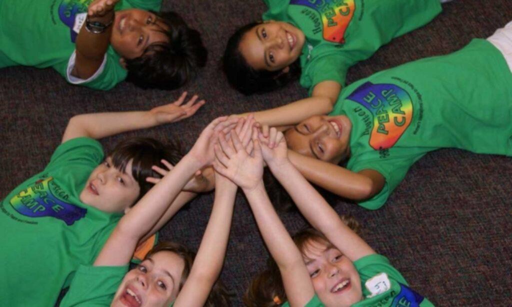 Peace Camp children lying on floor holding hands